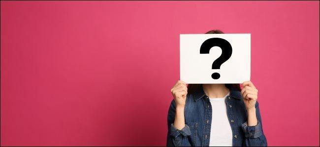 Una mujer sosteniendo un signo de interrogación frente a su rostro.