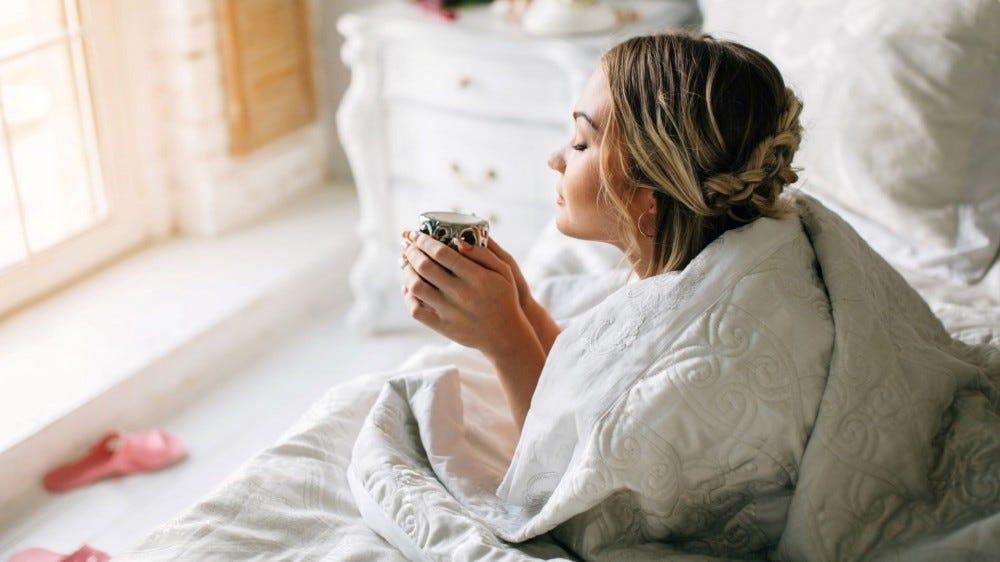 Una mujer tomando café en la cama por la mañana.
