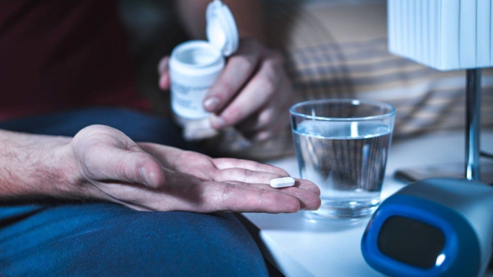 Un hombre que toma una pastilla de melatonina antes de acostarse.