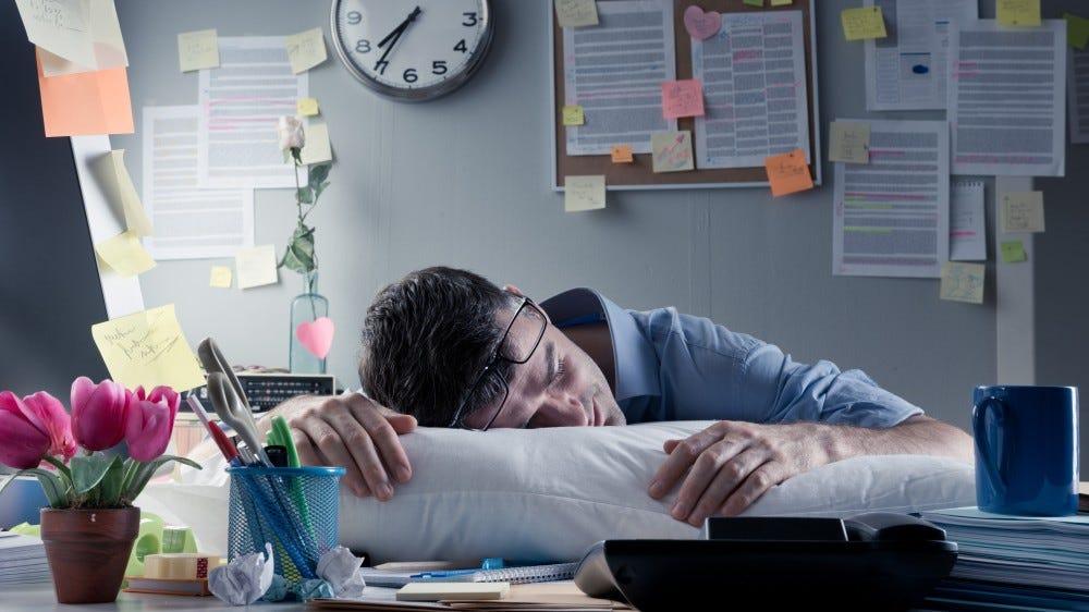 Un hombre dormido en su escritorio mientras trabaja desde casa.