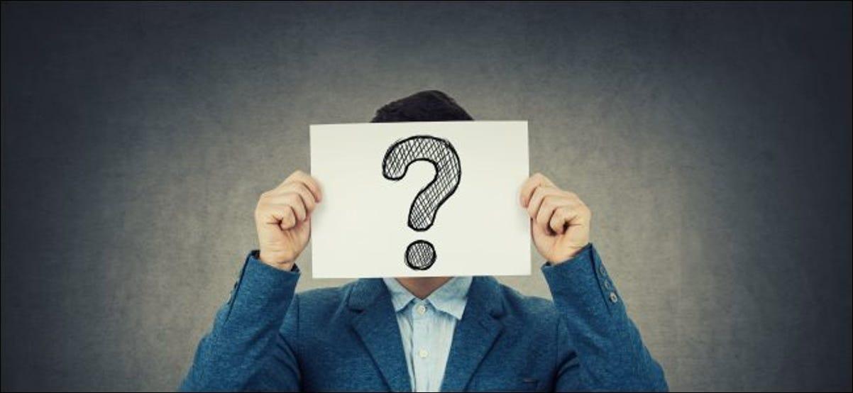 Una persona anónima sosteniendo un papel con un signo de interrogación frente a su cara.
