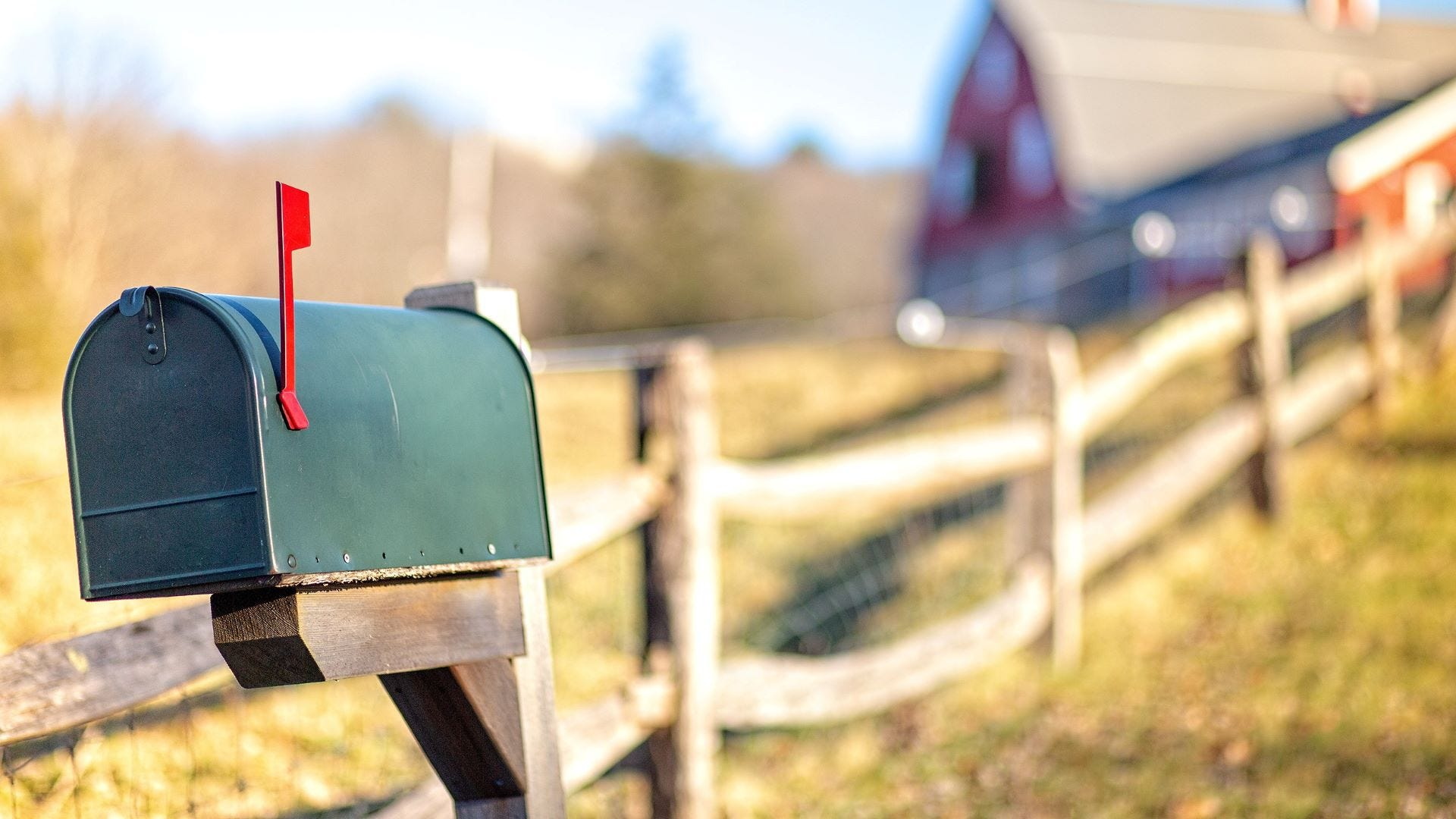 A raised flag on a mailbox with a barn in the background.