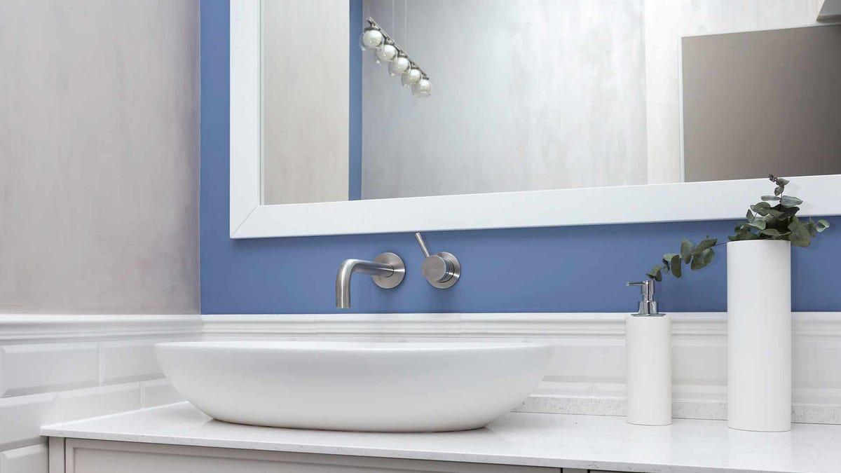 Un moderno baño blanco con una pared decorativa en azul bígaro.
