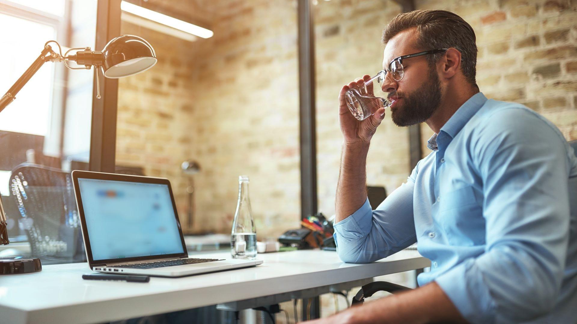 Un hombre bebiendo agua en su escritorio.