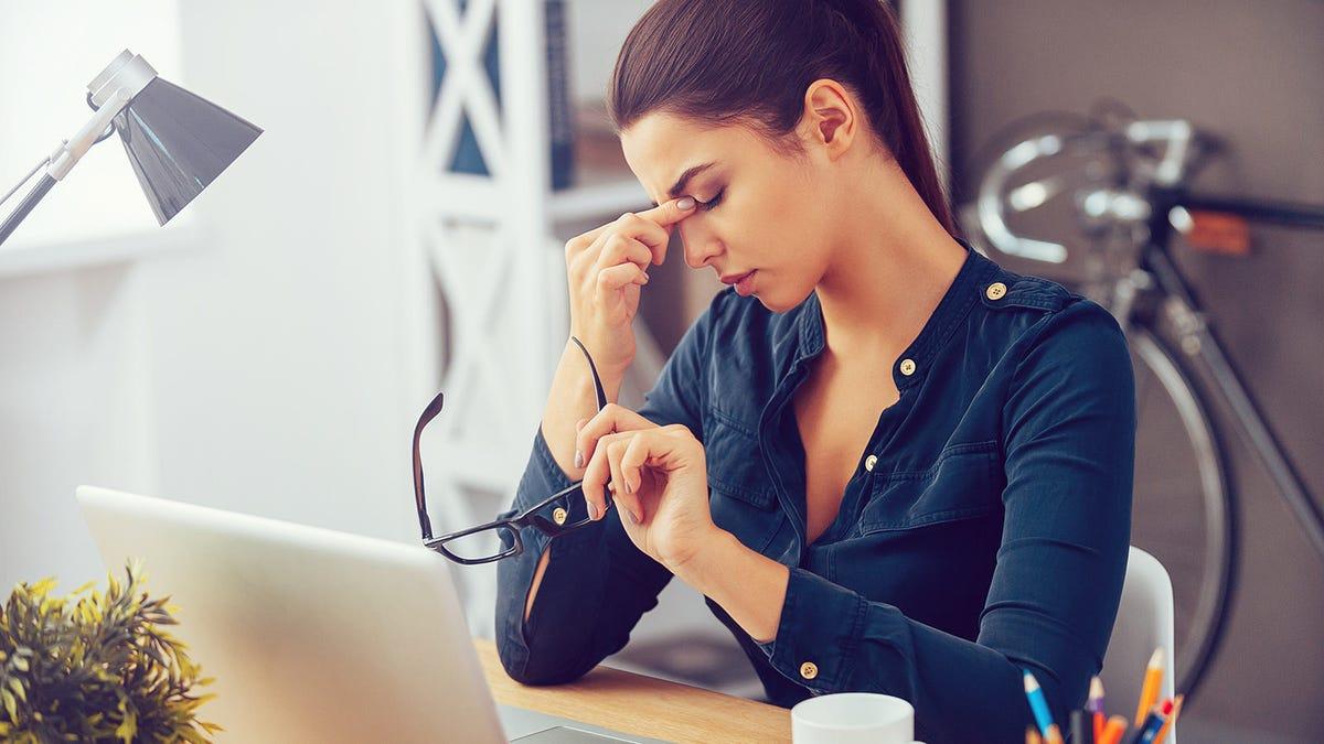 Una mujer cansada sentada en un escritorio con una computadora portátil abierta.
