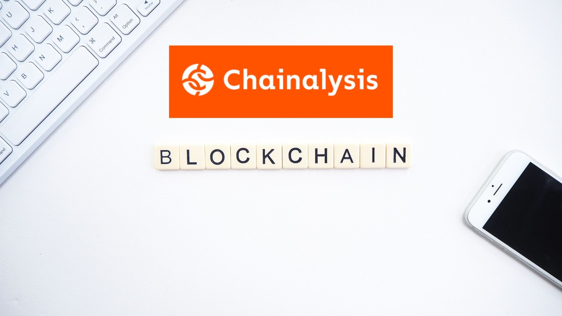 keyboard, mobile phone, blockchain in letters and Chainalysis logo