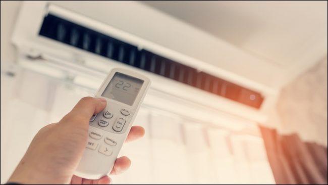 Una mano apuntando con un control remoto a un acondicionador de aire