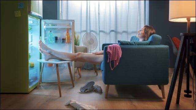 Mujer refrescándose delante de un frigorífico