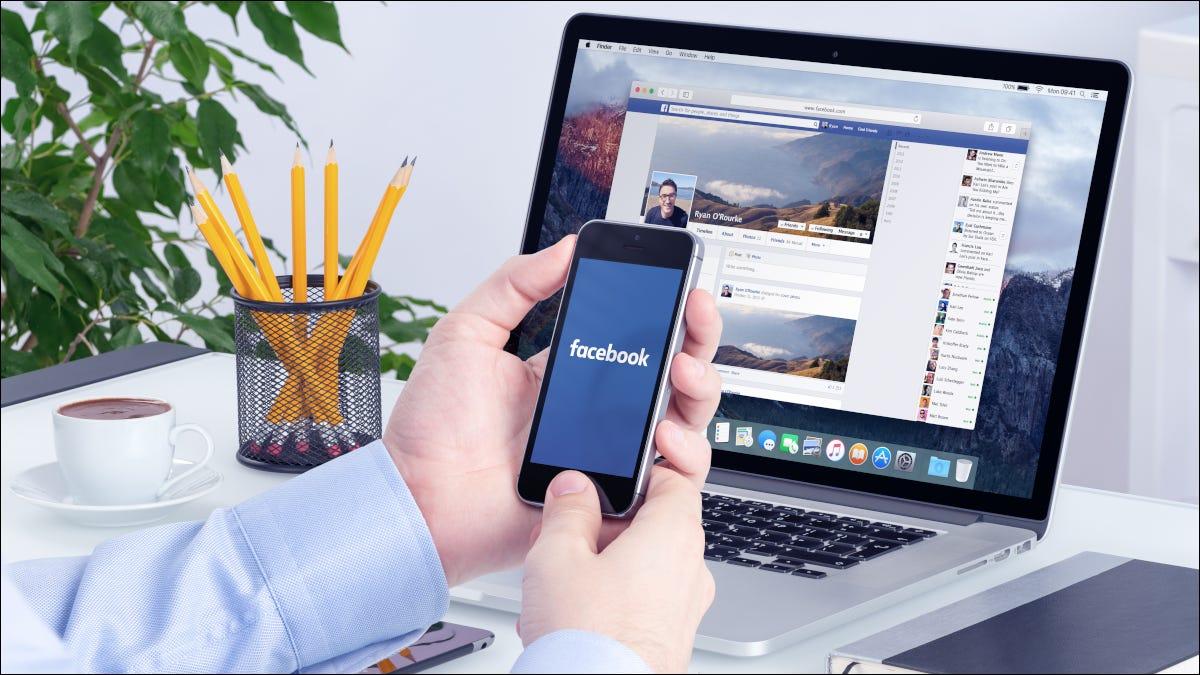Manos sosteniendo un teléfono inteligente frente a la computadora portátil con Facebook abierto
