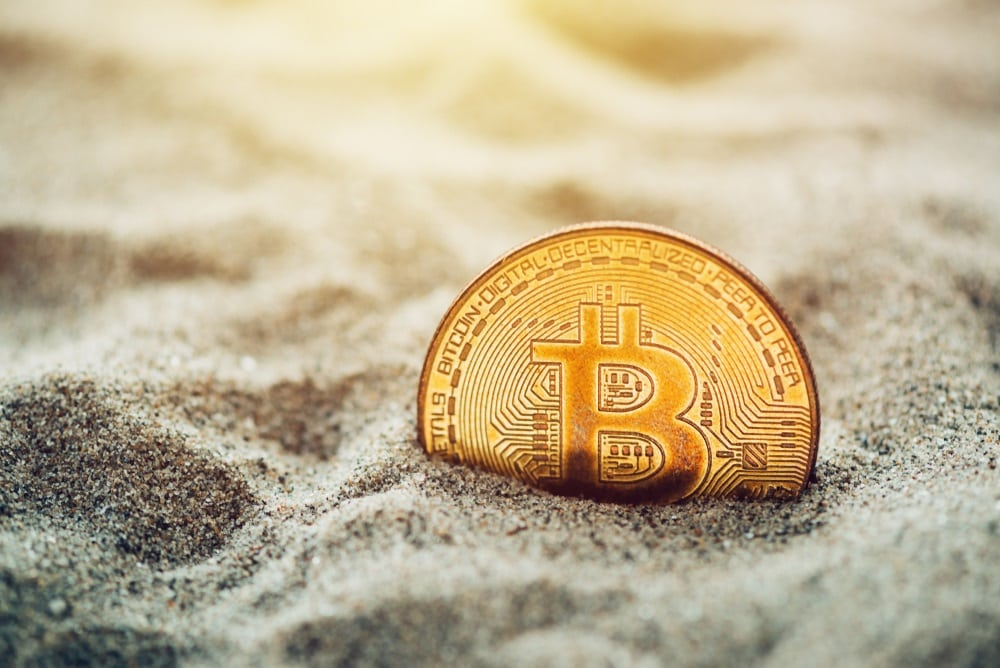 Picture of a bitcoin half-hidden in sand