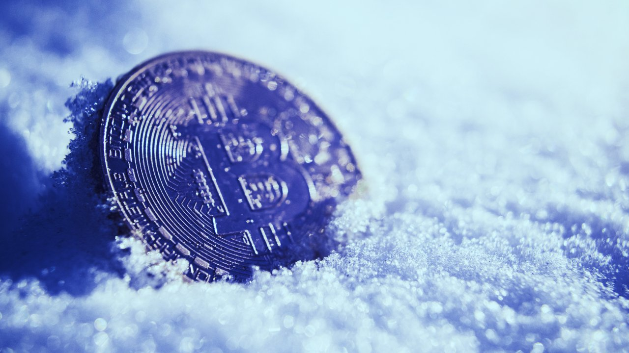 Picture of a bitcoin with snow surrounding it
