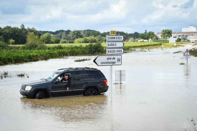 Imagen de un automóvil atascado cerca de una carretera inundada.