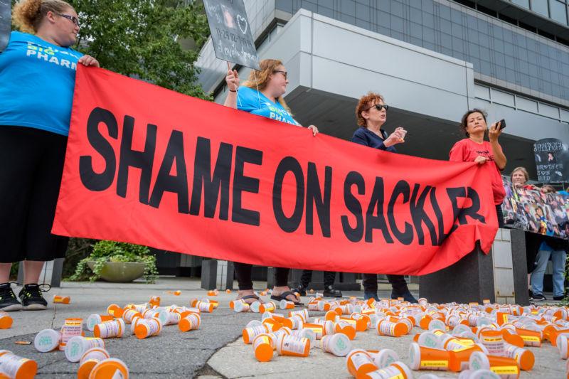 Los manifestantes sostienen una pancarta rodeados de frascos de recetas vacíos.