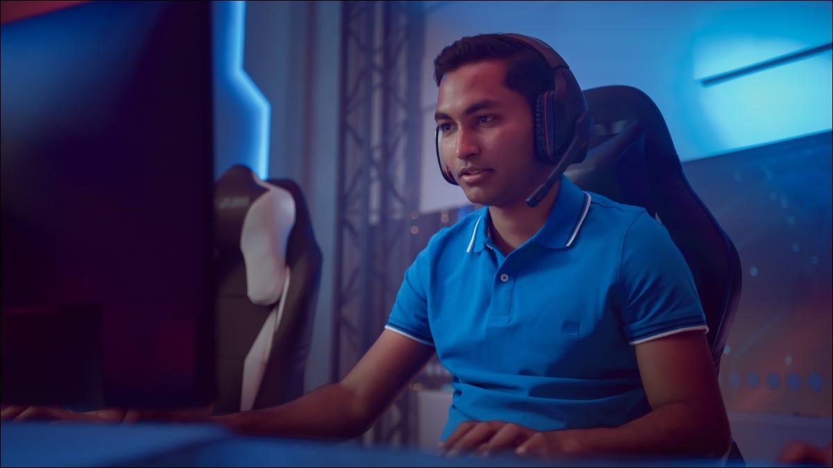 Jugador de deportes electrónicos masculino con auriculares mirando el monitor