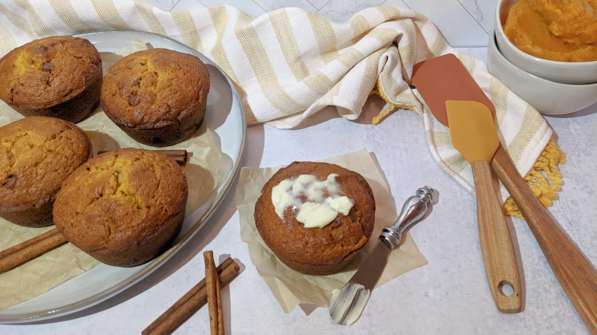Un muffin tibio con mantequilla derretida por encima, colocado al lado de un plato lleno de muffins tibios, unas espátulas raspadoras y un poco de calabaza ronroneada de fondo.