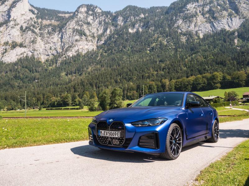 Un BMW i4 azul junto a unas montañas